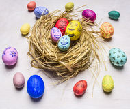 Colored ornamental eggs for Easter with painted faces lie in a nest wooden rustic background top view close up Stock Image