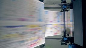 Colored pages moving on a line, top view. Paper moving on a typographical line