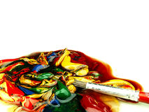Colored paint mixed on palette. Dirty brush in the foreground. royalty free stock image