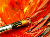 Colored paint mixed on palette. Dirty brush in the foreground. Royalty Free Stock Photo