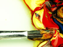 Colored paint mixed on palette. Dirty brush in the foreground. stock photos