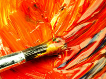 Colored paint mixed on palette. Dirty brush in the foreground. Royalty Free Stock Photography