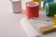 Colored paint pots and tools on white table elevated view royalty free stock photography