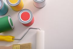 Colored paint pots and tools on white table top view royalty free stock photography