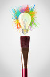 Colored paint splashes and lightbulb. Paintbrush close-up with colored paint splashes and lightbulb concept Stock Photos