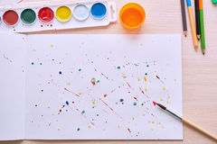 Colored paint on a white sheet and brush royalty free stock photos