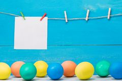 Easter eggs painted in different Colors on blue background with place for inscription on white paper royalty free stock image