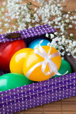 Colored painted eggs in a lilac basket Stock Images