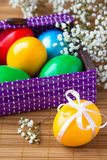 Colored painted eggs in a lilac basket Royalty Free Stock Photography
