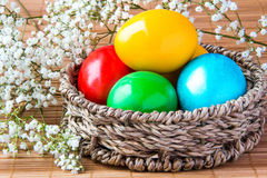 Colored painted eggs in a wattled basket with flowers Stock Photos