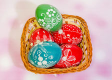 Colored painted romanian traditional Easter eggs in a rustic (vintage) basket, close up Royalty Free Stock Photos