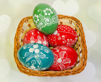 Colored painted romanian traditional Easter eggs in a rustic (vintage) basket, close up Royalty Free Stock Image