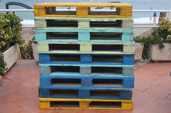 Colored pallets in front of the sea. Some colored pallets in front of the sea Royalty Free Stock Photography
