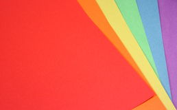 Colored Paper Background. Rainbow colored papers fanned out to fill the page with color Stock Images