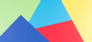 Color papers geometry flat composition background with yellow, green, red and blue tones Royalty Free Stock Photos