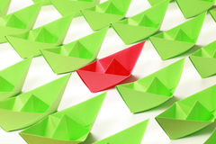 Colored paper boats. One red and several green paper boats on white background stock photos
