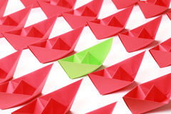 Colored paper boats. One green and several red paper boats on white background royalty free stock photography