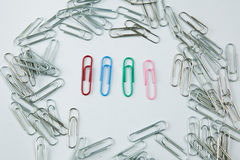 Colored Paper Clip among ordinary clips, which implies either it being a leader or a black sheep in group. Paper Clips arranged in messy way with isolated white Stock Image