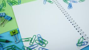Colored paper clip, smile binder clips and pencils on paper notepad