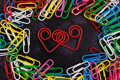 Colored paper clips isolated on dark background. Colored paper clips isolated on a dark background stock image