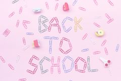 Colored paper clips on a pink background lined with the inscription - back to school. Laid erasers in the form of stationery - scissors, stapler, etc. top view royalty free stock photo