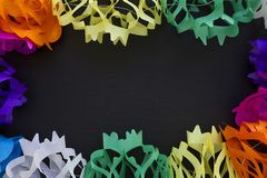 Paper garland background. Colored paper garland over a black background Royalty Free Stock Photography