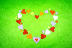 Colored paper hearts on a green cloth royalty free stock image