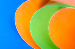Colored Paper. Orange and green colored paper on blue background royalty free stock images