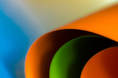 Colored Paper. Orange and green colored paper on blue/yellow background Stock Image