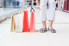 Colored paper packages on the floor in the mall, shopping concept. Soft focus background Stock Photos
