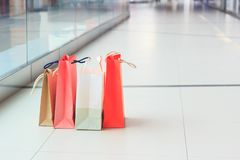 Colored paper packages on the floor in the mall, shopping concept. Soft focus background Stock Image