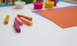 Colored paper and paints on the table stock illustration