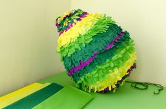Colored paper pinata on white wooden table.  Royalty Free Stock Photos