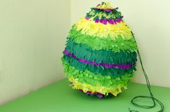 Colored paper pinata on white wooden table.  Stock Photos