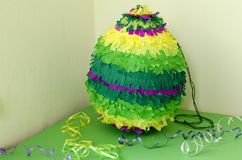 Colored paper pinata on white wooden table.  Royalty Free Stock Photography