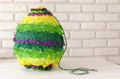 Colored paper pinata on white wooden table.  Royalty Free Stock Photo
