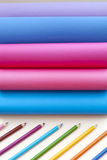 Colored paper rainbow and colored pencils. Group of colored paper sheets in unusual shape and colored pencils. Back to school concept Royalty Free Stock Photo