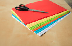 Colored paper and scissors on the table Royalty Free Stock Photos