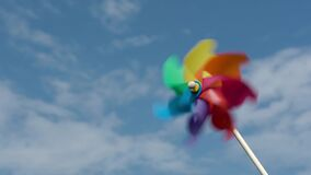 Colored paper screw rotates against a blue sky,slow motion