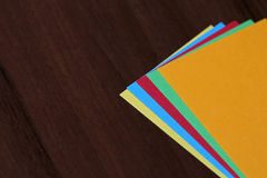 Colored paper on wood background Stock Photos