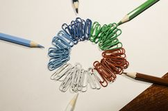 Colored paperclips in a circle and pencils stock photo