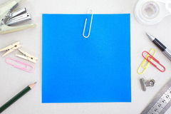 Colored papers with staple and stationery Royalty Free Stock Images