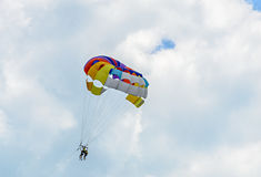 Colored parasail wing in the blue clouds sky, Parasailing. Also known as parascending or parakiting royalty free stock images