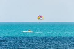Colored parasail wing pulled by a boat in the sea water, Parasailing also known as parascending or parakiting Royalty Free Stock Photo