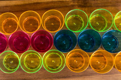Colored party cups - yellow, orange, pink and blue lined in three rows on a wooden board Royalty Free Stock Image