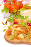 Colored pasta, cheese, spices, olive oil and tomatoes on board Stock Photography