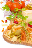 Colored pasta, cheese, spices and tomatoes on a wooden board Royalty Free Stock Photos