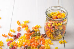 Colored pasta in a jar. And some scattered on the white wooden table Stock Images