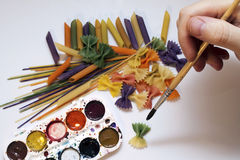 Colored pasta painted in different color brush. Draw Stock Photography