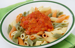 Colored pasta with tomato sauce. On plate Royalty Free Stock Photos